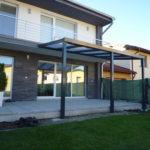 pergola, ktorá je upevnená o dom a vytvára rozšírený prístrešok pre posedenie na záhrade